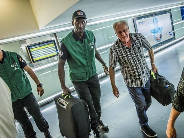 Uno dei «vigilants» in stazione a Bergamo porta le valigie di un passeggero